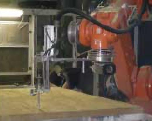Ein orangener Roboterarm bohrt Löcher in eine Holzplatte.