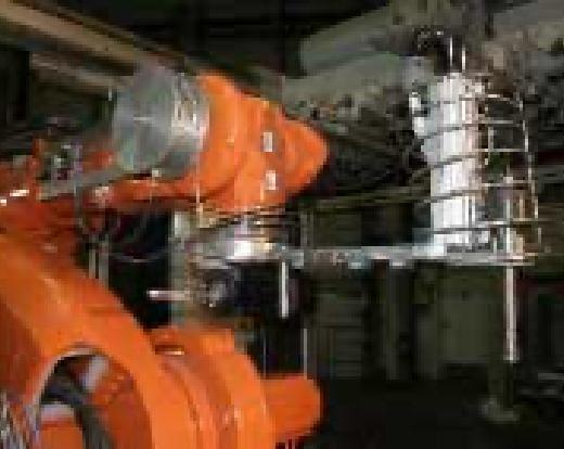 Eine orange Maschine mit silbernen Kabeln steht in einem dunklen Raum.