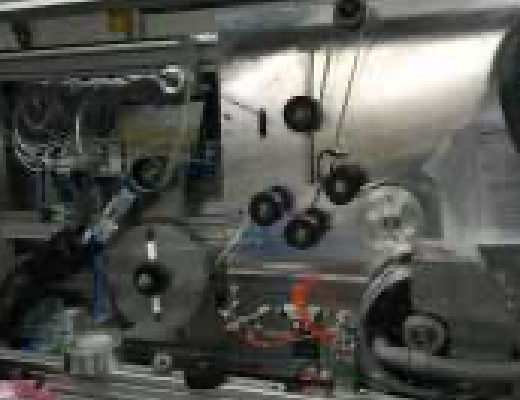 Eine aufwendige Fertigungsstation mit vielen Umlenkrollen an einer silbernen Metallwand befestigt.