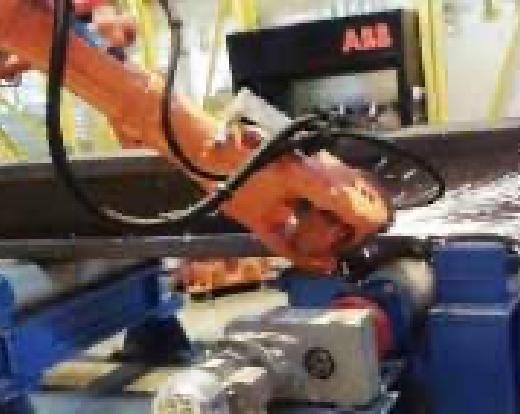 Ein orangener Roboterarm schleift Metall.