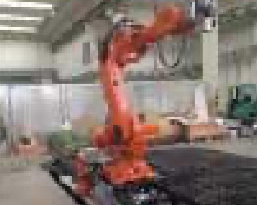 Ein großer orangener Roboterarm wird in voller Größe in einer Produktionshalle dargestellt.