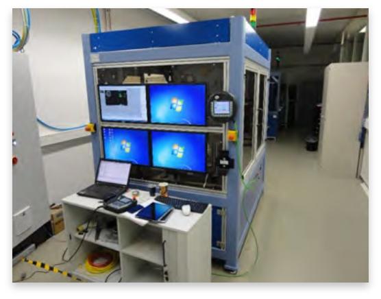 Vier große Monitore an einer Schaltzentrale sind zusehen. Davor steht ein Tisch mit einem Laptop.