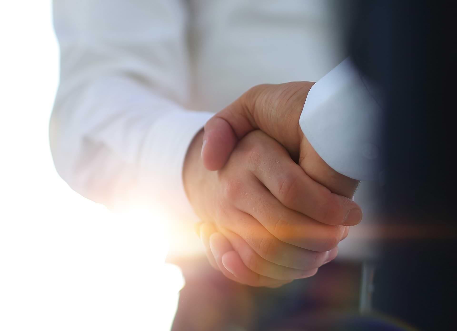 Zwei männliche Hände machen einen geschäftlichen Händedruck in einem hellen Hintergrund mit Sonnenschein.